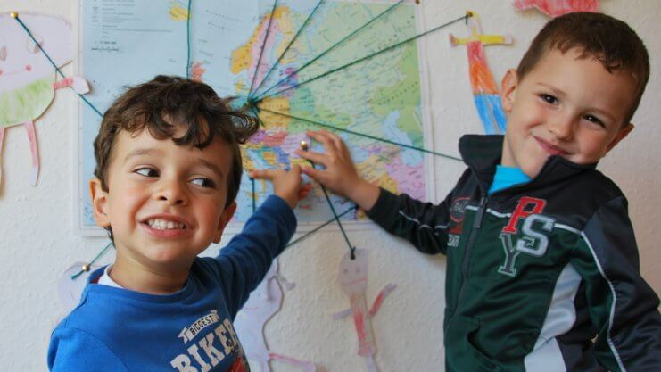 Zwei fröhliche Jungen zeigen auf eine Weltkarte an der Wand