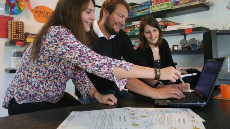 Drei Betreuungspersonen schauen sich etwas auf einem Laptop an