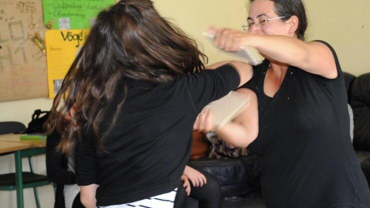 Ein Mädchen zerschlägt mit einem Karatehieb ein Holzbrett mit dem Unterarm