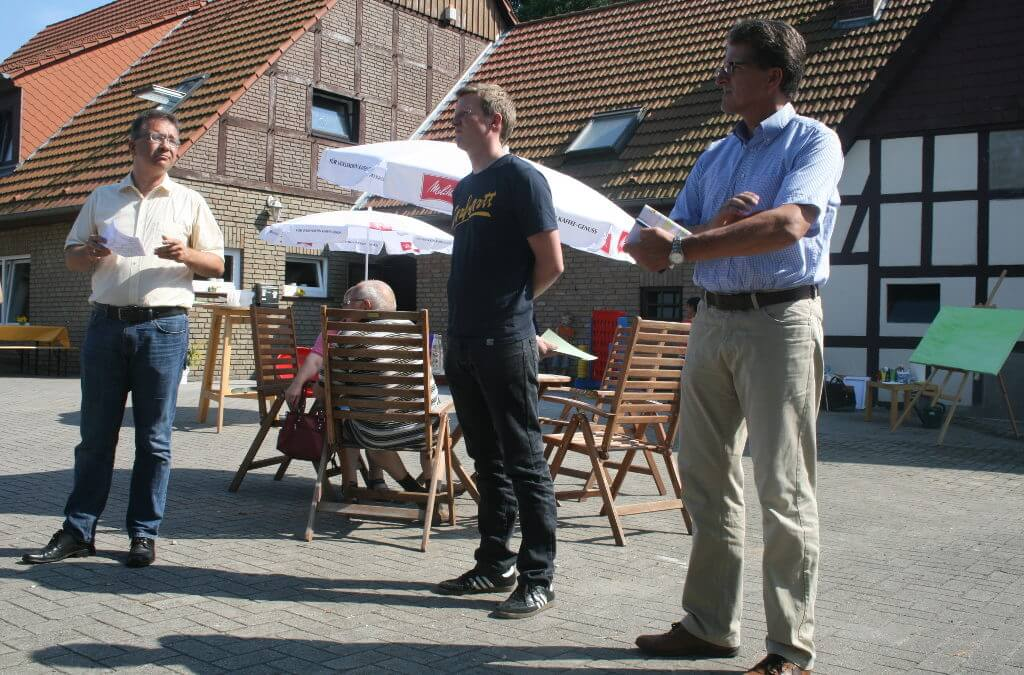 Drei Männer stehen auf dem Hof vom Haus Ellerbeck