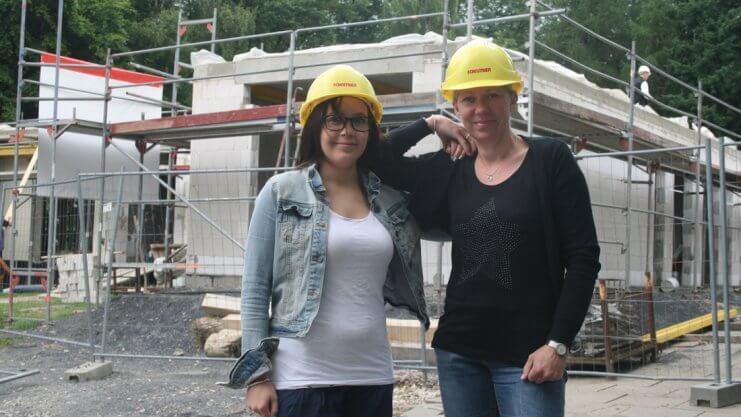 Zwei Frauen mit Bauhelm vor einer Baustelle