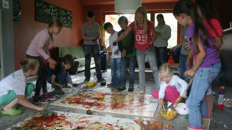 Kinder gestalten auf dem Boden zwei große Bilder