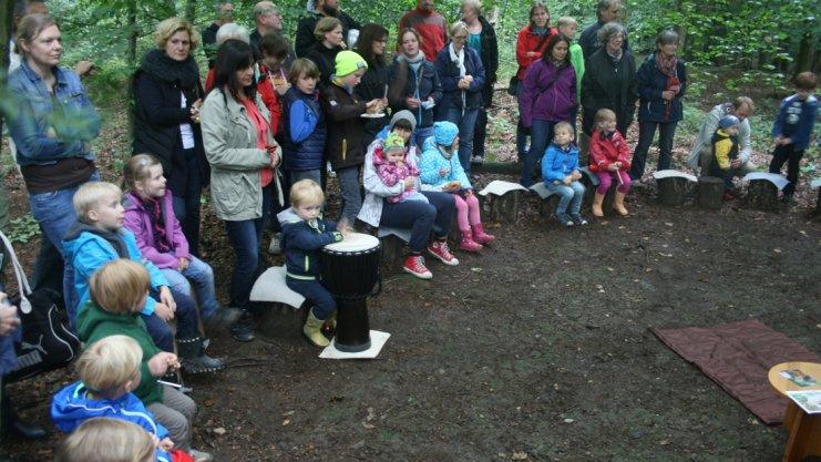 Kinder und Erwachsene sitzen im Kreis auf Baumstümpfen im Wald