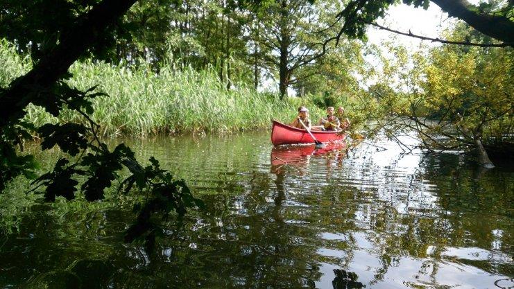 Kinder fahren im Kanu im Wasser