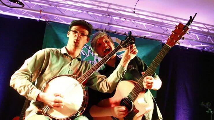 Zwei Künstler auf der Bühne mit Musikinstrumenten