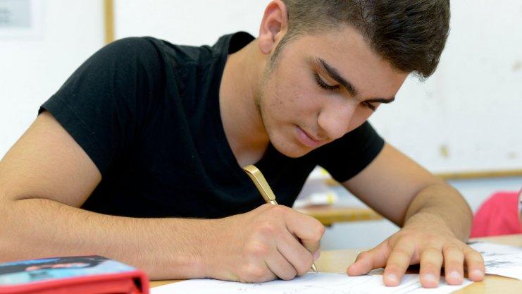 Junger Mann schreibt auf einem Arbeitsblatt