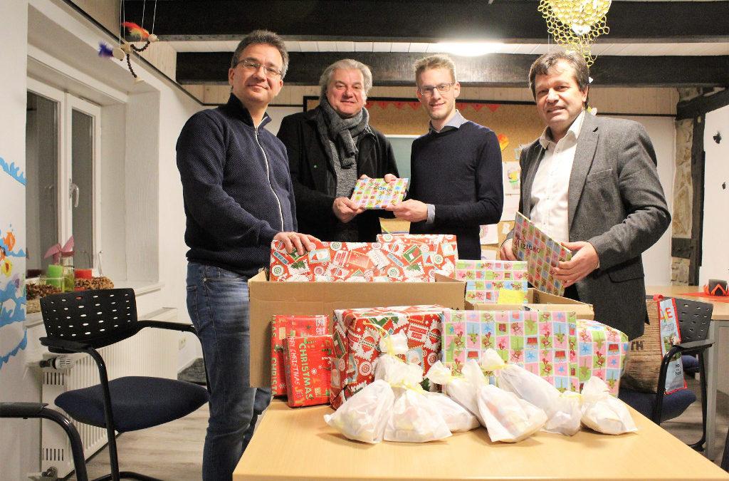 Mitglieder der LINKE und Tim Ellmer stehen hinter Weihnachtsgeschenken