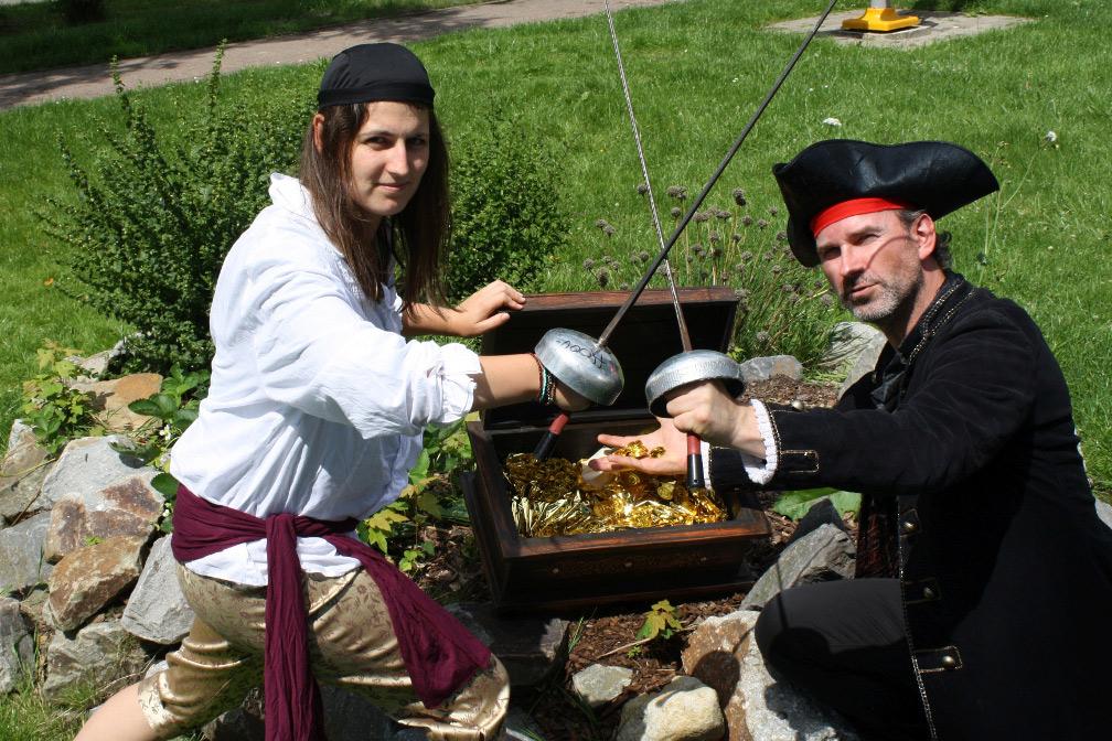 Zwei als Piraten verkleidete Betreuungspersonen knien vor einer Schatztruhe voller Gold