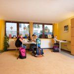 Drei Jungen und eine Betreuungsperson bei den Hausaufgaben
