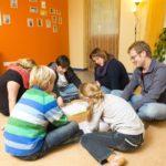 Betreuungspersonen und Kinder beim Lernen auf dem Boden