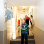 Kinder laufen fröhlich hüpfend durch de Flur der Tagesgruppe