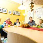 Kinder und Betreuer essen gemeinsam am Tisch