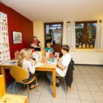Kinder basteln zusammen am Tisch Häuser