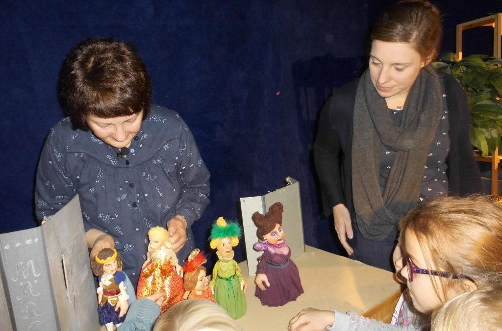 Kinder und Erwachsene betrachten Figuren eines Figurentheaters