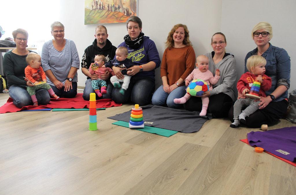 Eltern mit ihren Kindern und Betreuungspersonen sitzen im Kreis