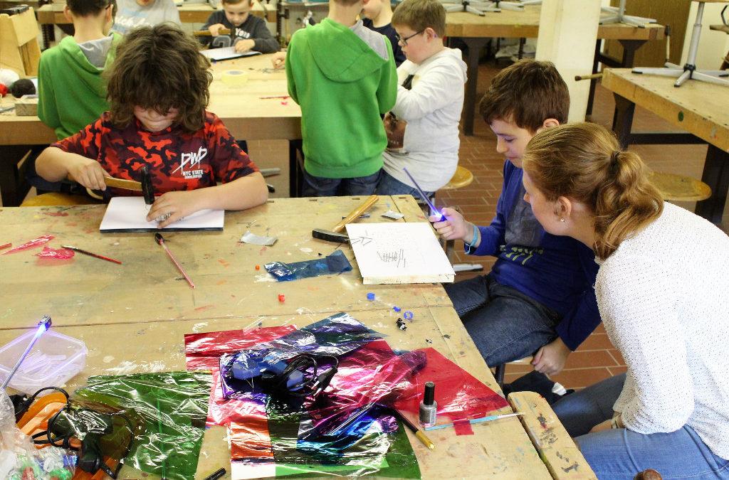 Kinder werken mit Betreuungsperson