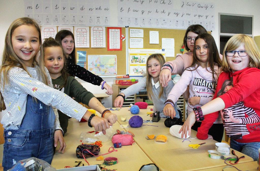 Gruppenfoto von sieben Mädchen mit ihren Armbändern