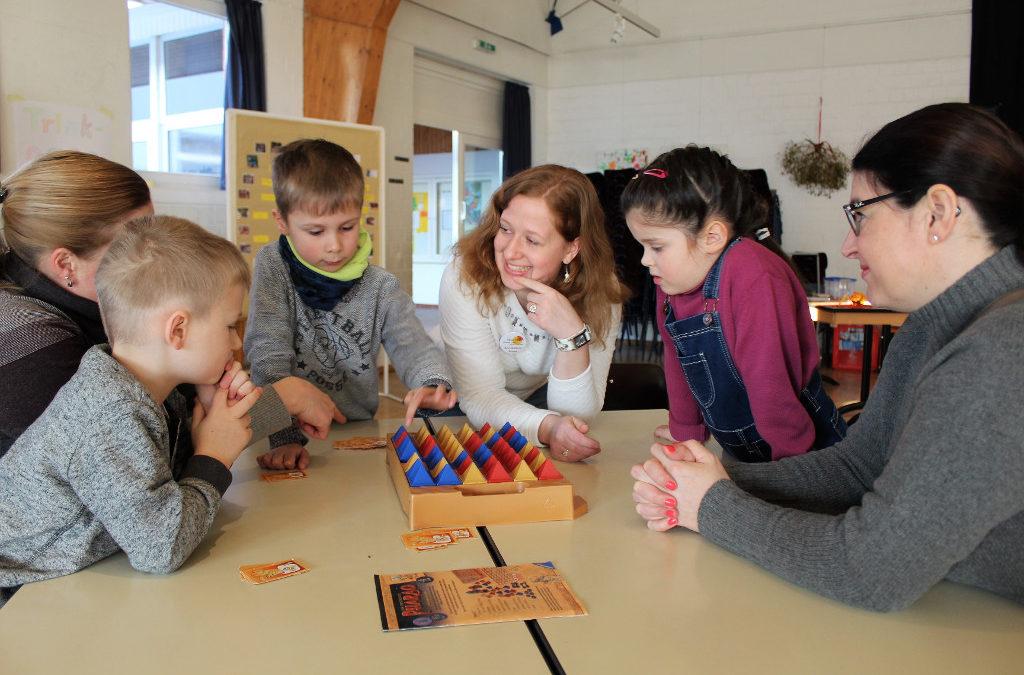 Betreuungspersonen und Kinder spielen gemeinsam ein Spiel