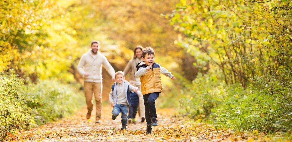 Zwei Kinder laufen fröhlich durch einen herbstlichen Wald mit ihren Eltern