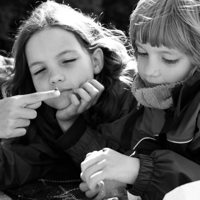 Schwarzweiß Bild von zwei Kindern, die sich Marienkäfer anschauen