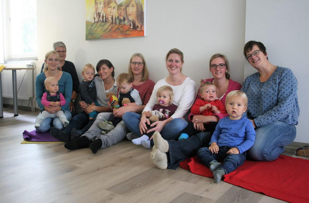 Eltern mit ihren kleinen Kindern und Betreuungsperson auf dem Boden sitzend
