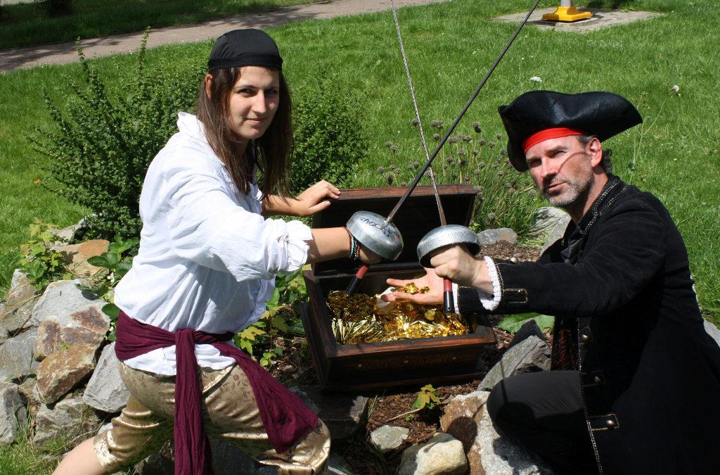 Zwei als Piraten verkleidete Betreuungspersonen knien vor einer Schatzkiste voller Gold