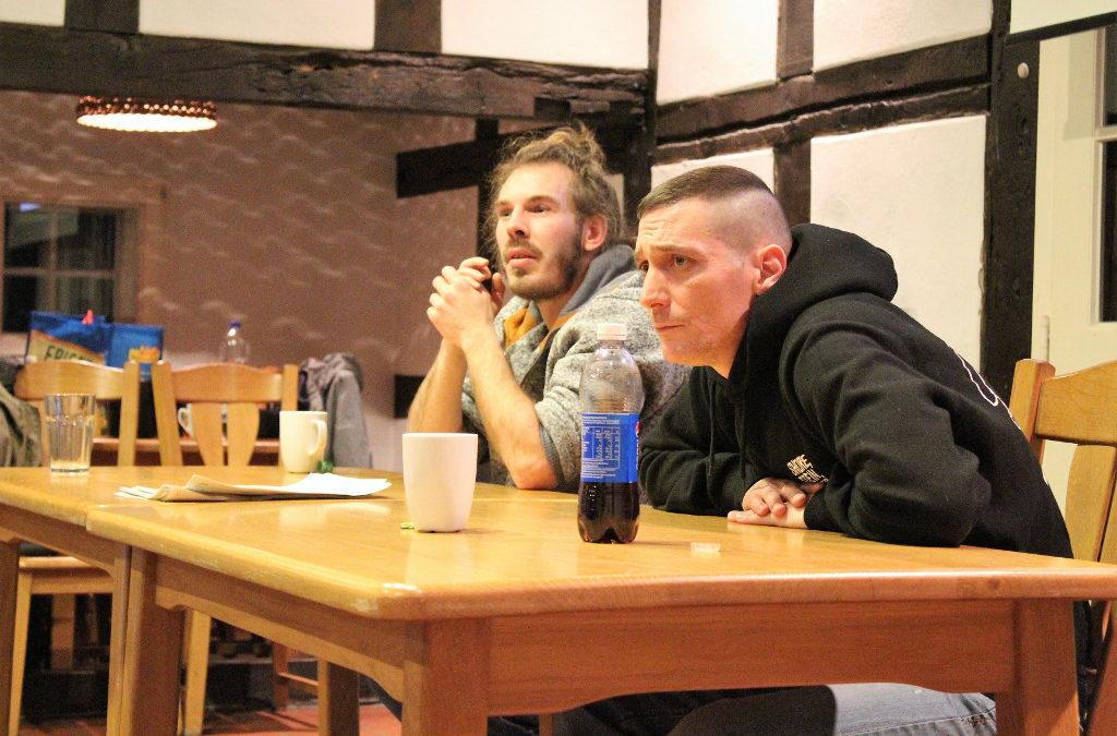 Zwei Männer sitzen am Tisch und sprechen mit ihren Zuhörern