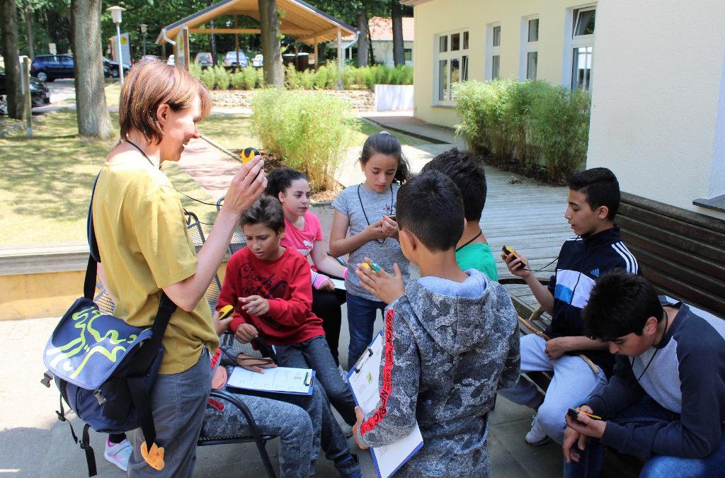 Betreuungsperson mit Kindern beim Geochashing