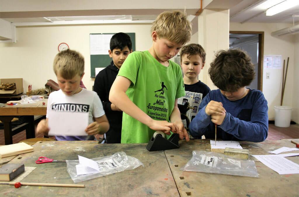 Fünf Jungen basteln an einer Werkbank mit Holz
