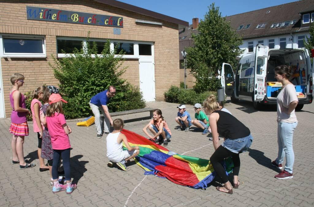 Kinder auf dem Hof der Wilhelm-Busch-Schule helfen beim Aufbau zum Aktionstag