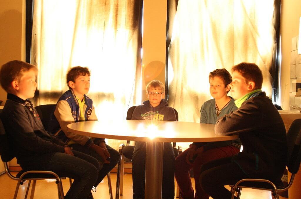 Fünf Jungen sitzen an einem runden Tisch