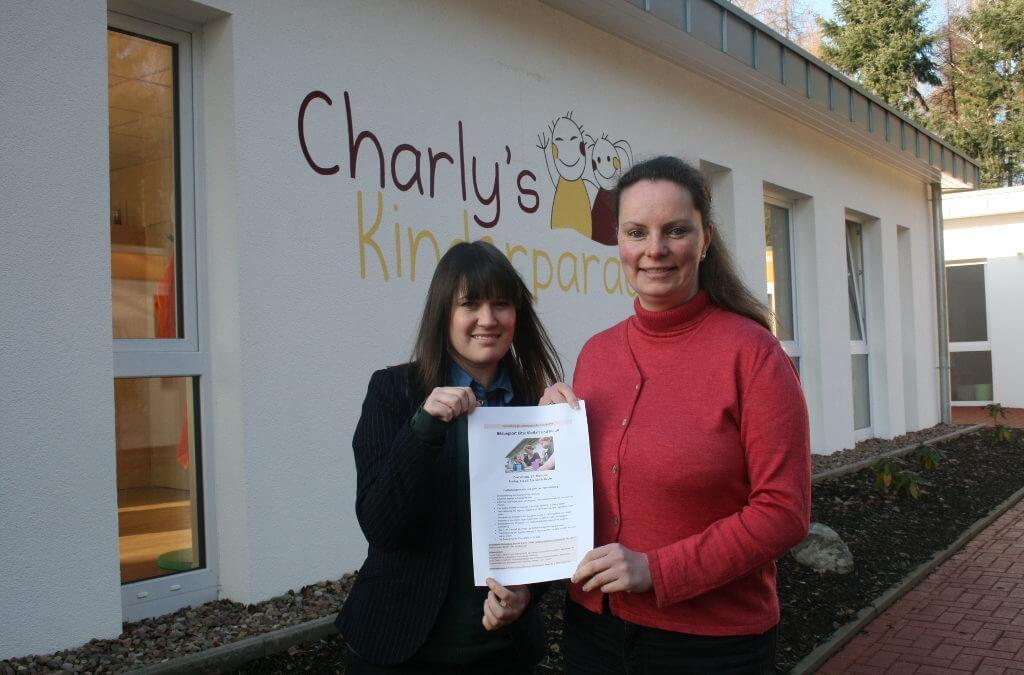 Zwei Frauen halten ein Programm vor dem Charly's Kinderparadies in die Kamera