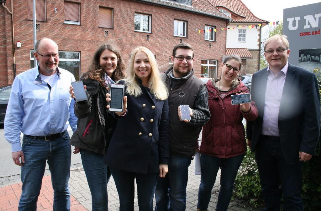 Gruppenfoto von Bohmtern, die ihr Handy in die Kamera halten