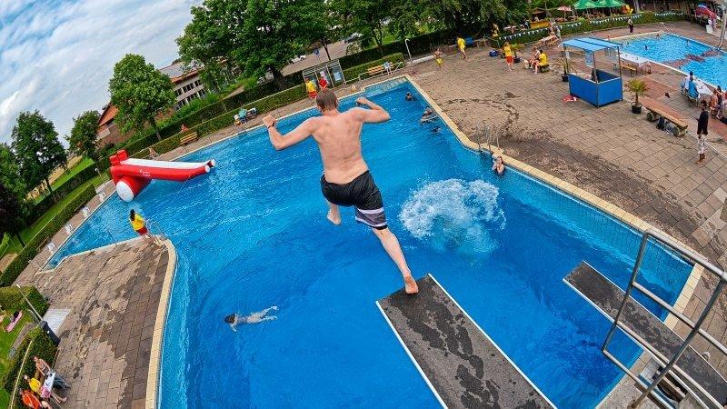 Ein Mann springt gerade vom Brett ins Freibadbecken