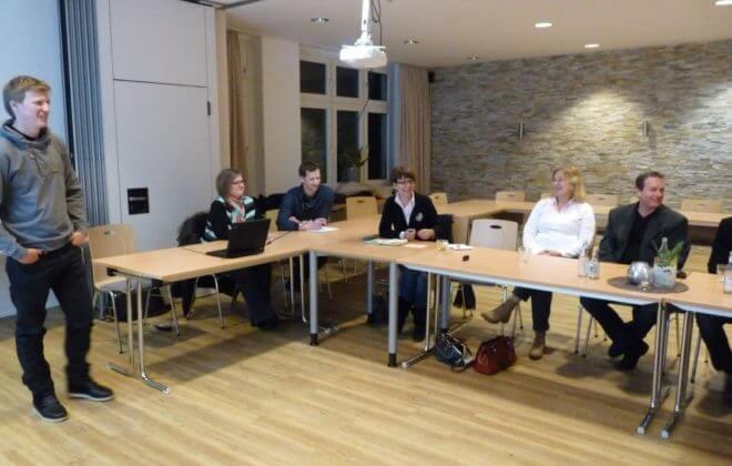 Menschen sitzen bei einer Informationsrunde am Tisch