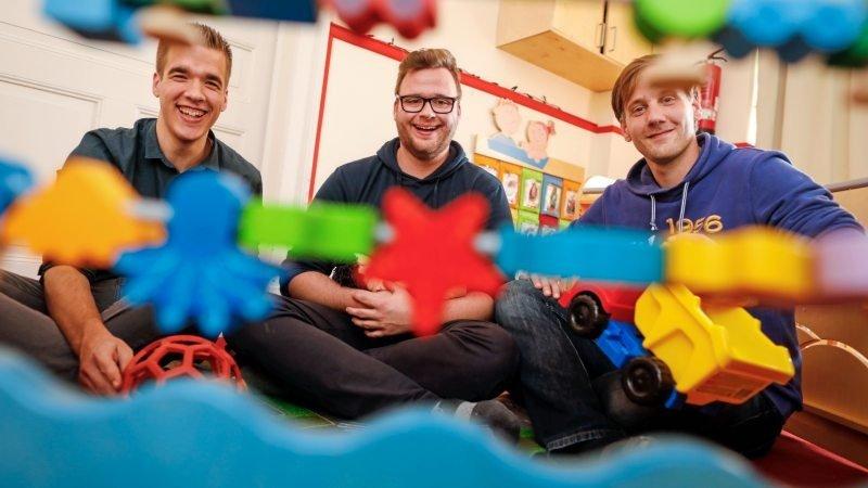 Drei männliche Erzieher sitzen auf dem Boden und lachen in die Kamera