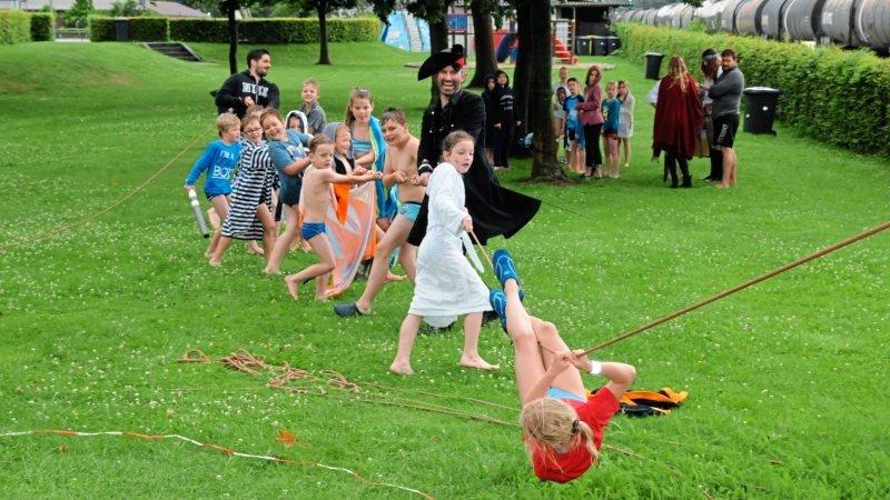 Eine Gruppe von Kindern ziehen an einem Seil während ein Mädchen sich daran entlang hangelt