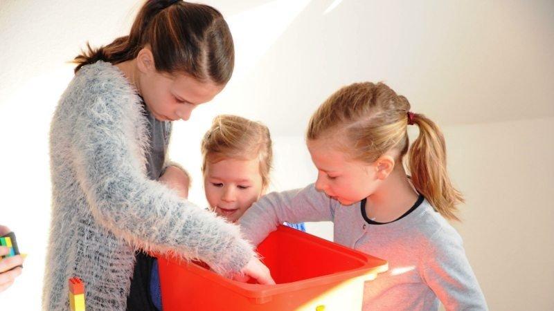 Mädchen verschiedenen Alters suchen Lego auf einer Orangenen Kiste