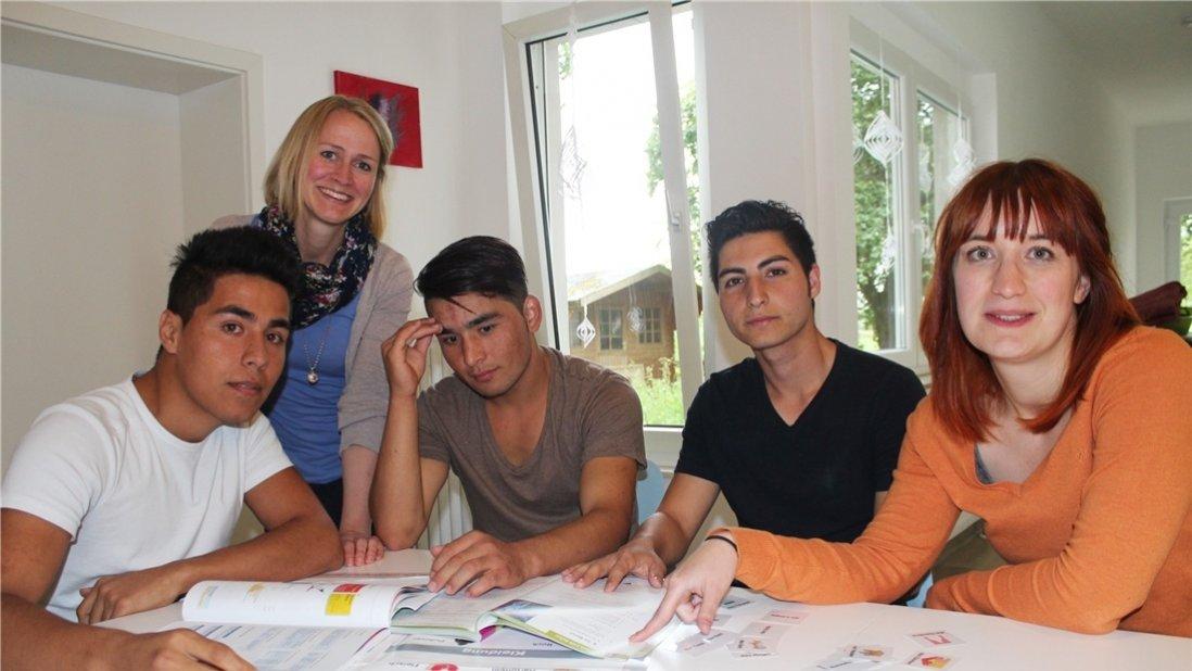 Junge Frauen und Männer sitzen am Tisch und lernen