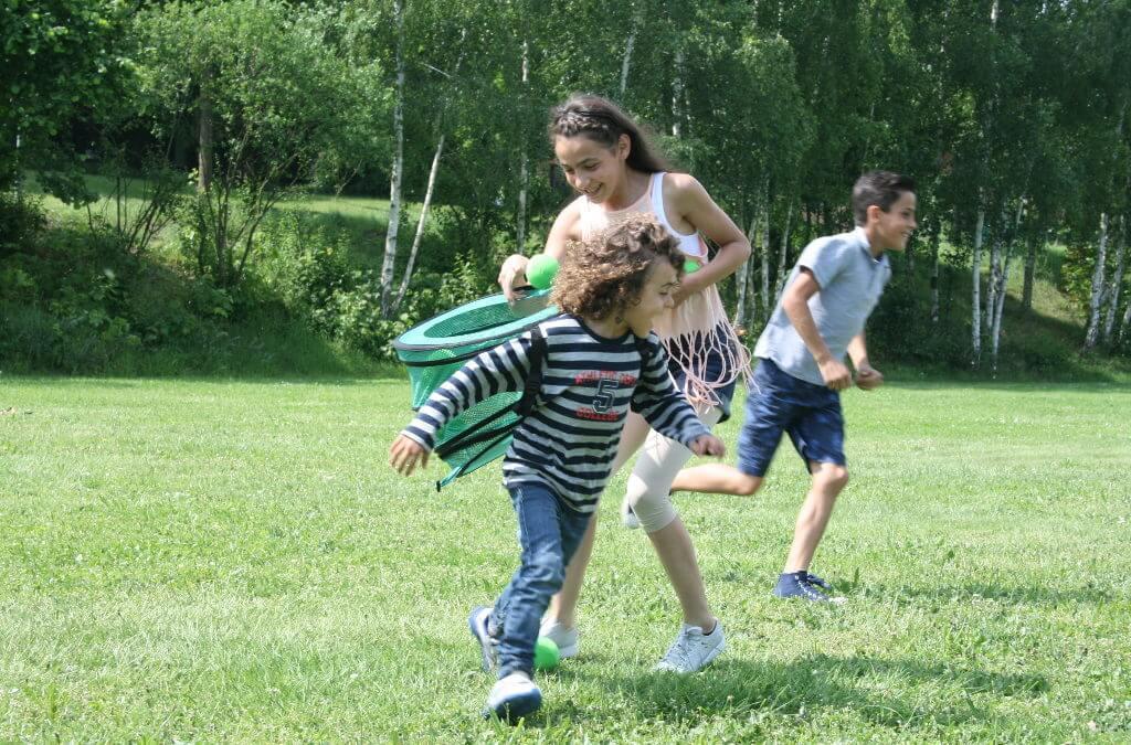 Kinder spielen ein Ballspiel auf der Wiese