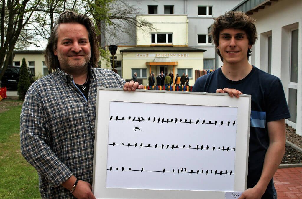 Zwei Männer halten eine die Naturfotografie des Jahres vor dem Haus Sonnenwinkel in die Kamera