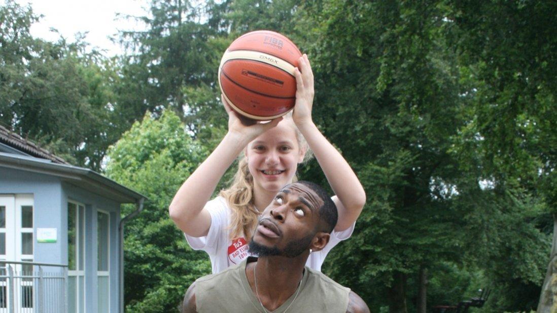 Ein Mädchen hält einen Ball über den Kopf von Torrell Martin