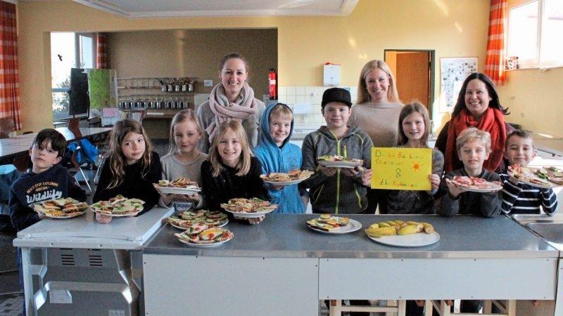 Schulkinder und Betreuungspersonen mit gefüllten Tellern am Pausenkiosk