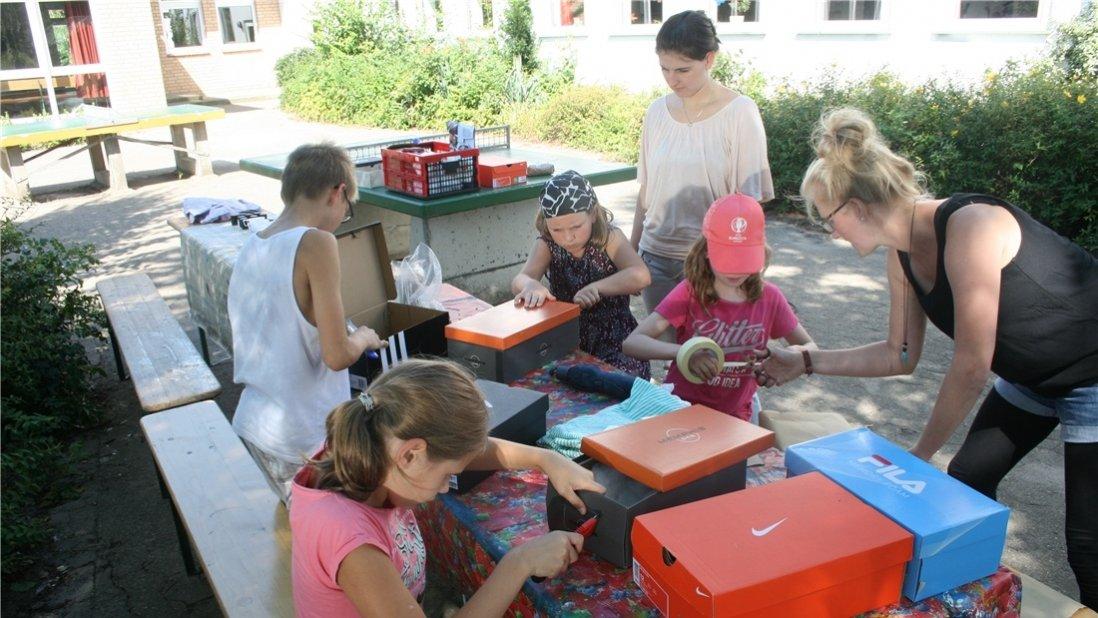 Kinder und Erwachsene basteln draußen mit Schuhkartons