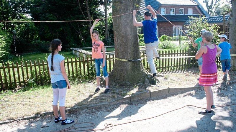 Kinder und Erwachsene bauen eine Slackline an einem Baum auf