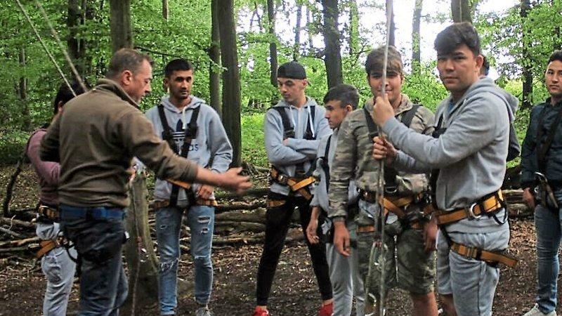Junge Männer stehen in Klettergeschirren im Kletterwald