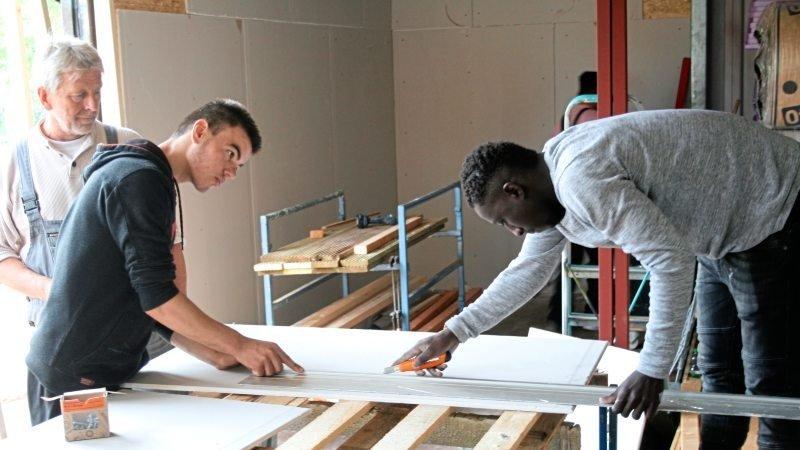 Zwei Flüchtlinge schneiden unter Anleitung eine Rigipsplatte zurecht