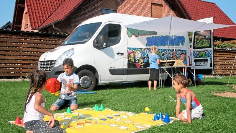 Kinder spielen auf der Wiese vor dem Mobilen Jugendtreff