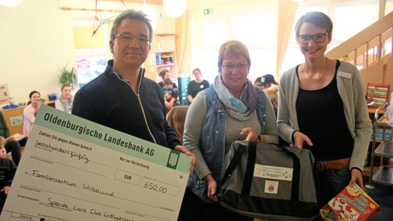 Gruppenaufnahme mit Scheck zur Spende für das Familienzentrum Wirbelwind