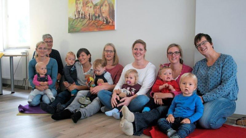 Eltern mit Kindern und Betreuungsperson auf dem Boden lächeln in die Kamera